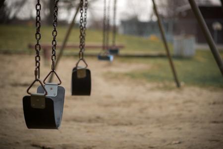columpio: Columpios para niños cuelgan vacío ralentí en un parque en un día nublado aburrido. Foto de archivo