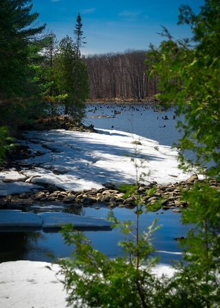 Canadian wilderness landscape of a snow covered rocky shore of an Ontario lake in springtime. Standard-Bild