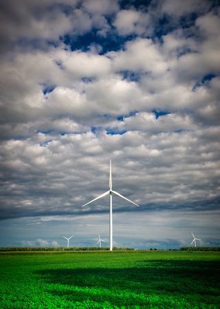 A white wind-turbine at a wind farm stands tall in the distance under a cloudy sky and over a rich, green field.