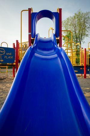 Looking up toward the top of a blue plastic slide at a children's playground. Standard-Bild