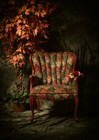 Studio image of a colorful, antique empty chair shot in a chiaroscuro style of lighting, sitting next to artificial plant.