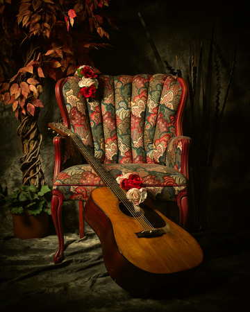 A vintage acoustic guitar leans against an empty, antique patterned armchair. Shot in chiaroscuro style lighting.