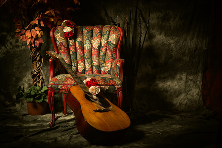 A vintage acoustic guitar leans against an empty, antique patterned armchair. Shot in chiaroscuro style lighting with room for your copy.