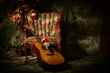 muebles antiguos: Una guitarra ac�stica de la vendimia se inclina contra un, antig�edad sill�n estampado vac�a. Herido de bala en la iluminaci�n de estilo claroscuro con espacio para su copia. Foto de archivo