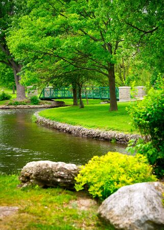 Footbridge: A small footbridge crosses a stream amidst the lush, green foliage of a beautiful park.