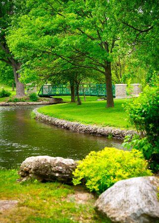 A small footbridge crosses a stream amidst the lush, green foliage of a beautiful park.