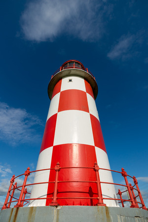 Perspective shot looking up toward the top of a tall red and white checkered lighthouse.