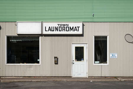 The front exterior and entrance to an old rundown generic with sign.