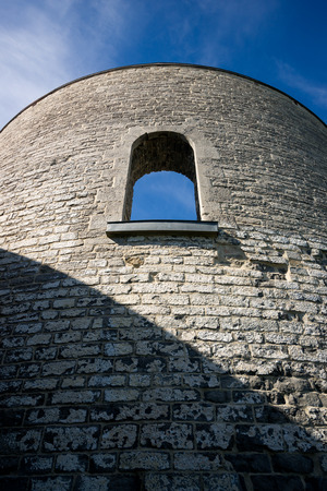 Perspective shot looking up toward the top of an ancient stone tower wall with arched window.