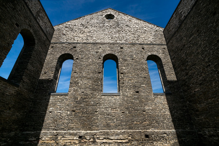 Looking up at the towering stone wall of an ancient church ruins with three gothic windows.