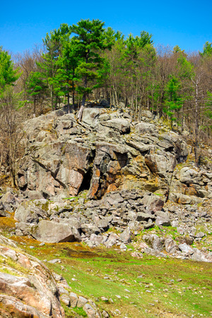 stoney: Landscape image of a very large tree covered rocky cliff in the heart of the Canadian shield. Stock Photo