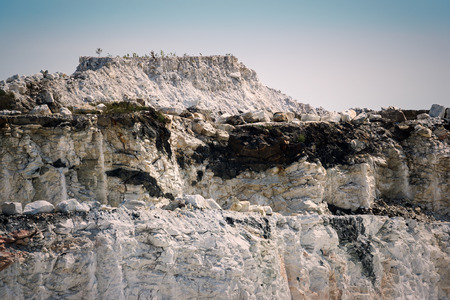 The steep and rocky, chalky looking cliffs of an open-pit marble mine.