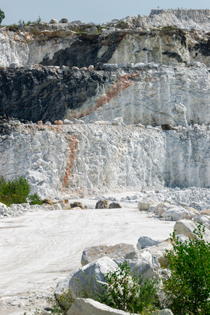 three layered: The white, chalky rock of a three tiered layered cliff at an open-pit marble mine. Stock Photo