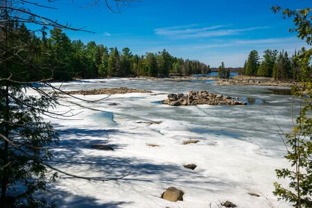 The spring thaw melts the snow covering a lake inlet in the wilderness of Ontario, Canada. Standard-Bild