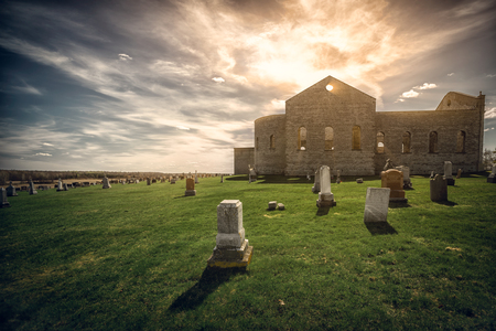 roofless: An old graveyard (cemetery) with the ruins of an ancient stone church in the background shot under evening light.