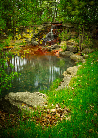 Timed exposure of a small beautiful grottolike rocky waterfall oasis and pond surrounded by the deep green of a lush paradiselike forest.