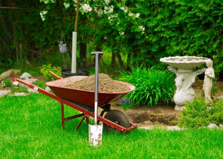A red Wheelbarrow sits full of dirt in a lush green garden as spring gardening work is underway. Standard-Bild