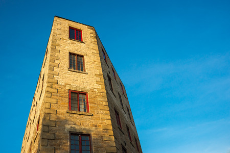 An oddly shaped building featuring vintage architectural detail rises up against a bright blue sky with plenty of space for your copy. Standard-Bild