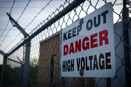 A warning sign on a barbed wire chainlink fence which reads  Keep out danger high voltage.