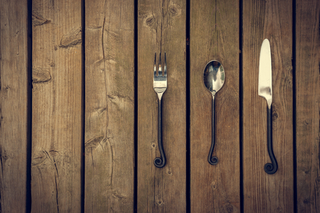 Antique style cutlery, a fork, spoon and knife with twirled, rapier like work metal stems against a natural wooden board background. Standard-Bild