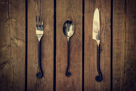 Vintage style cutlery, a fork, spoon and knife with twirled design metal-work handles against a natural wooden board background.