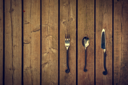 rule of thirds: Vintage antique style cutlery, a fork, spoon and knife with twirled design metal stems against a natural wooden board background. Stock Photo