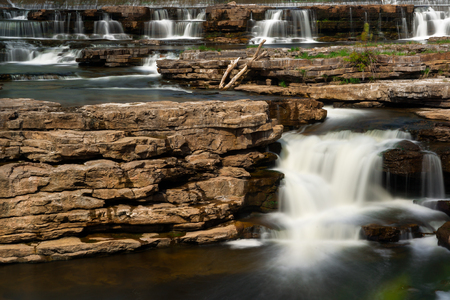 Beautiful scenery of many multiple waterfalls flowing and cascading over a rocky area, captured in a timed exposure.