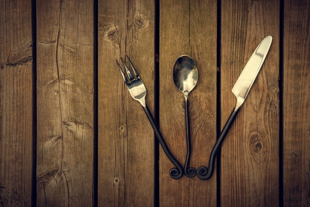 Vintage antique style cutlery, a fork, spoon and knife with twirled design metal stems fanned out on a natural wooden board background. Standard-Bild