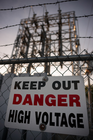 A sign reading Keep Out, Danger, High Voltage, affixed to a chain-link, barbed wire fence.