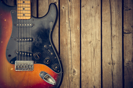 A beat up and dirty vintage electric guitar body against a natural wood-grain boards background.