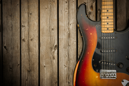 A beat up, dirty and road-worn old vintage electric guitar body against a natural wood-grain boards background.