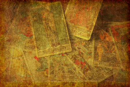cartomancy: A textured, grunge background image of a group of scattered tarot cards from the major arcana.