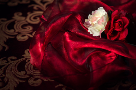 flower background: A white and red silk rose and carnation sits atop a wadding of luxurious, flowing silk material.