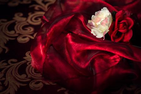 Een witte en rode zijden roos en anjer zit boven op een watten van luxe vloeiende zijde materiaal.