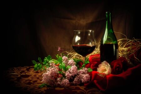 An elegant scene with a glass of red wine next to wine bottle surrounded by lilac, roses and luxurious cloth.