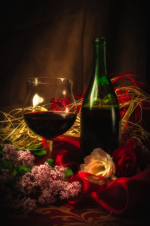 sumptuous: An elegant scene with a glass of red wine next to wine bottle surrounded by lilac, roses and luxurious cloth in soft, warm lighting. Stock Photo