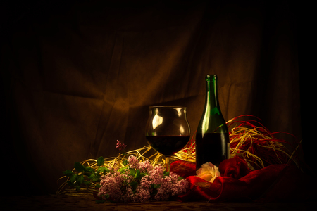 sumptuous: An elegant scene with a glass of red wine next to wine bottle surrounded by lilac, roses and luxurious cloth and soft lighting. Stock Photo