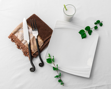 A clean, white fancy plate lies empty on a white background cloth in a simple, beautiful place setting with knife and fork, sprigs of leaves and small drink. Standard-Bild