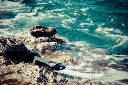 emigranti: Searuined scarpe perse sulla costa Archivio Fotografico