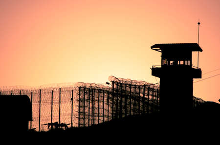 barbed wires: Silhouette of barbed wires and watchtower of prison in Neapolis, Crete, at sunset
