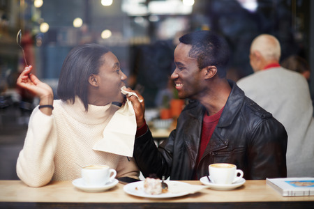 shop window: Portrait of young couple in love at a coffee shop, boyfriend wiping her mouth with a napkin at breakfast, romantic couple having fun together, two friends smiling sitting in cafe