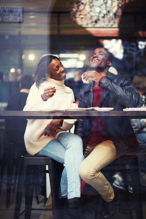 Beau couple dans l'amour de boire du café et de rire dans un café, amis heureux un café ensemble, rire jeune couple dans le café, ayant un bon moment ensemble, vue à travers la fenêtre d'un café Banque d'images