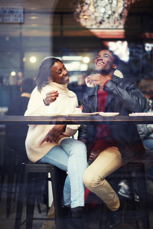 Beautiful couple in love drinking coffee and laughing in coffee shop, happy friends having coffee together, laughing young couple in cafe, having a great time together, view through cafe window