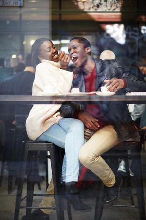 hombre tomando cafe: amigos elegantes felices que tienen café juntos, riendo pareja de jóvenes en el café, con un gran tiempo juntos, ver a través de ventana del café, retrato de la joven pareja en el amor en una cafetería, la gente que se divierte