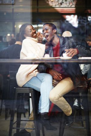 man drinking coffee: Happy stylish friends having coffee together, laughing young couple in cafe, having a great time together,view through cafe window, portrait of young couple in love at a coffee shop, people having fun Stock Photo