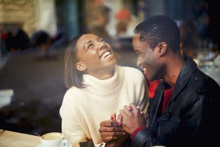 Két ember a kávézóban élvezi az időt töltenek egymással, boldog elegáns barátok kávézott együtt, nevető fiatal pár kávézó, miután egy nagy idő együtt, megtekintheti a kávézó ablakon
