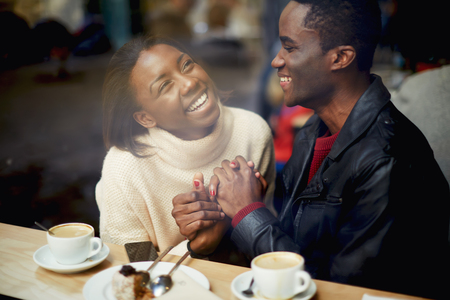 Laughing young couple in cafe, having a great time together, view through cafe window, romantic couple having fun together, best friends smiling sitting in cafe, view through cafe window Stock Photo