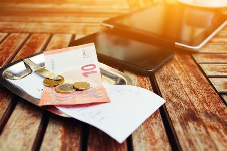 cheque en blanco: Mock-up con cheque factura y dinero, teléfonos inteligentes y la pantalla táctil de la tableta digital en el escritorio de madera, aparatos con pantalla en blanco vacío, rotura de trabajo del hombre de negocios, la flama de la luz del sol