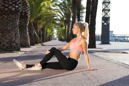 rest day: Portrait of a young fit woman dressed in sportswear taking break after active physical exercises outdoors, athletic female in sport bra enjoying rest after fitness training outside in sunny summer day Stock Photo