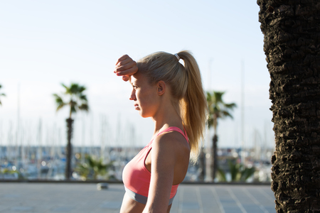 female jogger: Tired female jogger rubbing her forehead while resting after active morning running in the fresh air around the city, young athletic woman dressed in sport bra taking break after workout outdoors